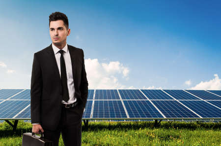 solarenergy: Salesman or businessman holding briefcase on solar power panels background. Manager of sun energy company