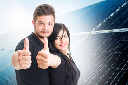 solarpower: Happy couple showing like on solar power photovoltaic panel background  as green energy solution concept