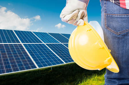 Engineer holding yellow construction helmet on solar power panels background