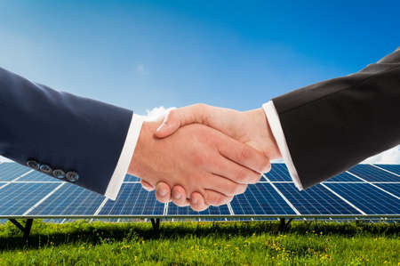 solarpower: Businessmen handshake on solarpower photovoltaic panel background as bio-energy business team agreement