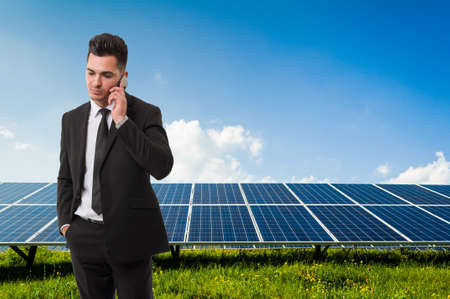 solarenergy: Modern businessman and salesman talking on the phone on solar power panels background Stock Photo