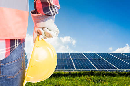 Engineer holding hardhat on solar power photovoltaic panels background. Build future renewable energy solution systems concept