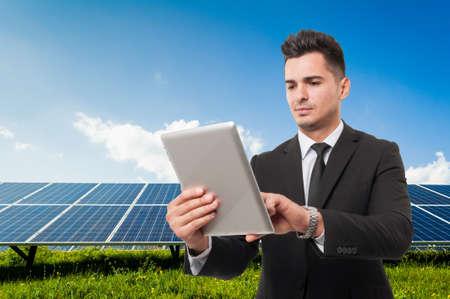 solarenergy: Modern businessman holding wireless tablet on solar power panels background