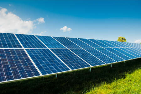 green fields: Solar power panels on green field with blue sky and copy space and text area Stock Photo