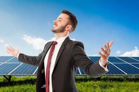 solarenergy: Happy smiling businessman with wide outspread or outstretched arms on solarpower photovoltaic panel background