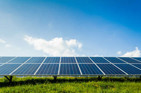 solarenergy: Solar panels on green field and blue sky, Renewable sun power concept