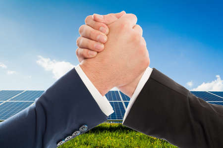 solarpower: Businessmen handshake as teamwork on solarpower photovoltaic panel background. Renewable energy partnership agreement