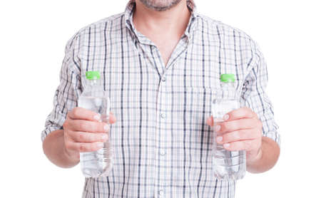 summer heat: Drink water during summer heat concept with man holding two bottles isolated on white