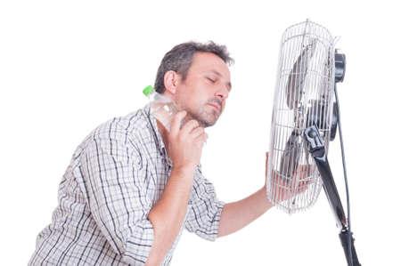 sudando: El hombre se refresca abajo delante del ventilador soplante con una botella de agua fría en el cuello