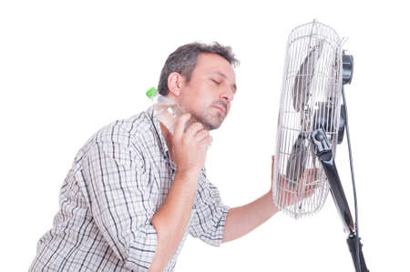 Man cooling down in front of blowing fan holding a bottle of cold water on the neck