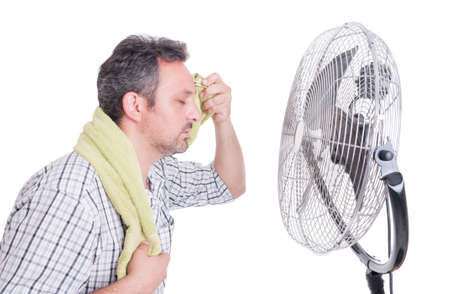 Man wiping sweaty forehead in front of cooling fan as hot summer dehydration concept
