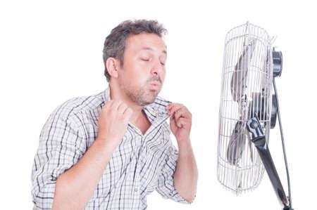 Hombre sudoroso abriendo camisa en frente de ventilador de refrigeración como refrescante en concepto de verano caliente Foto de archivo - 43028952