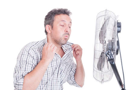 estado del tiempo: Hombre sudoroso abriendo camisa en frente de ventilador de refrigeración como refrescante en concepto de verano caliente