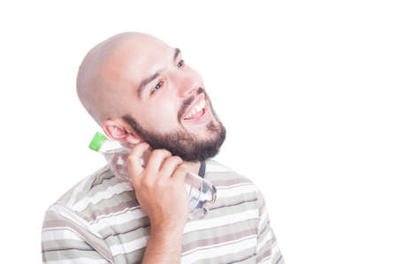 heat wave: Smiling man cooling neck with cold water in plastic bottle in summer season heat wave concept Stock Photo