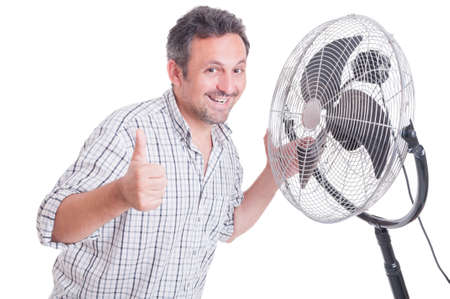 Smiling man showing like gesture in front of blowing cooler as summer heat concept Stock Photo