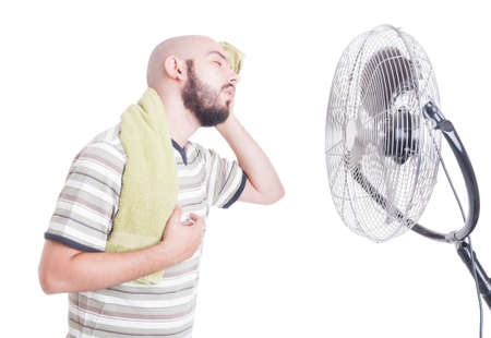 summer heat: Heated man wiping sweat of forehead using a towel in front of cooler as summer heat concept Stock Photo
