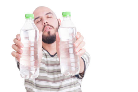 dehydration: Thirsty man holding two bottles of cold water as hydration or dehydration in summer heat concept