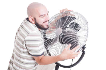 Sweaty and heated man hugging blowing fan or cooler isolated on white