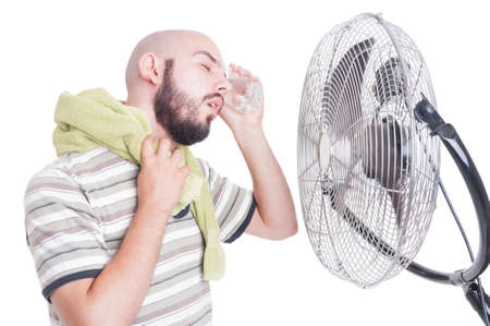 Man cooling his head with cold water bottle and fan or blowing cooler