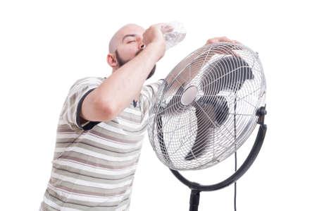 dehydration: Man drinking water near blowing fan as summer heat dehydration concept