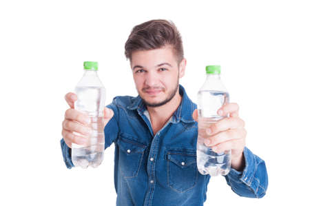 man drinking water: Handsome male model holding two bottles of cold water in summer heat season as dehydration concept