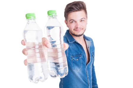 summer heat: Handsome male model offering two bottles of cold water in summer heat season as dehydration concept Stock Photo