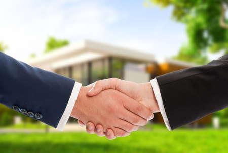 saludo de manos: Apret�n de manos en el fondo la casa al aire libre como negocio de bienes ra�ces o concepto de venta