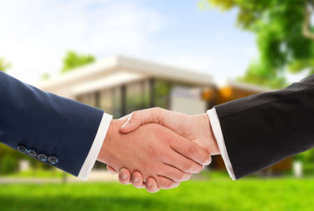 Handdruk op huis outdoor achtergrond als onroerend goed deal of verkoop concept
