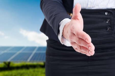 partnership power: Business woman offer handshake on solar power field background. Partnership for green energy concept