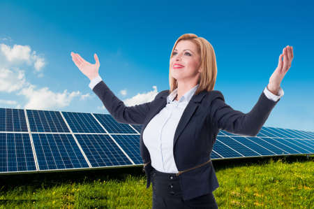 solarpower: Successful solar power and green energy saleswoman smiling confident with arms outspread or outstretched Stock Photo
