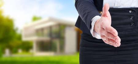 broker: Oferta de apretón de manos en el fondo la casa al aire libre como concepto de bienes raíces. Mujer agente de bienes raíces o corredor