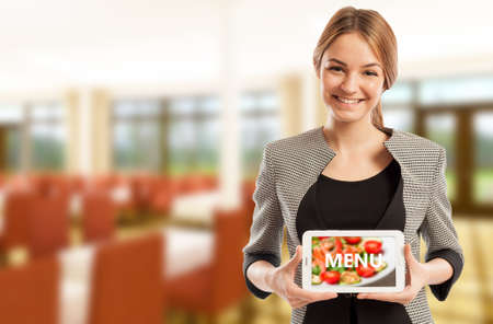 Woman modern restaurant manager holding tablet with menu on dining room background
