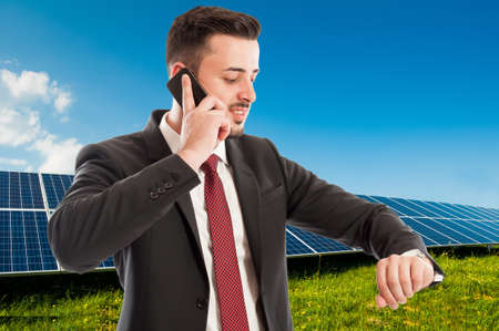 solarenergy: Busy businessman or salesman using phone and checking time on photovoltaic field background
