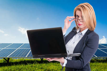 solarenergy: Businesswoman with solar power plant in background holding laptop. Green energy company manager Stock Photo