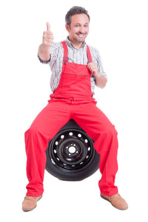 thumbup: Mechanic showing like gesture or thumb-up sitting on car wheel tire isolated on white