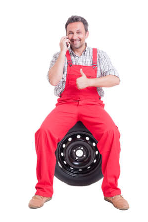 vulcanization: Mechanic talking on phone and showing like. Contact auto service or tire vulcanization company Stock Photo