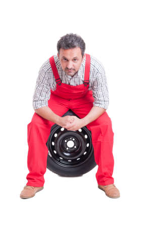 taking a break: Mechanic resting and taking a break sitting on a tire isolated on white Stock Photo