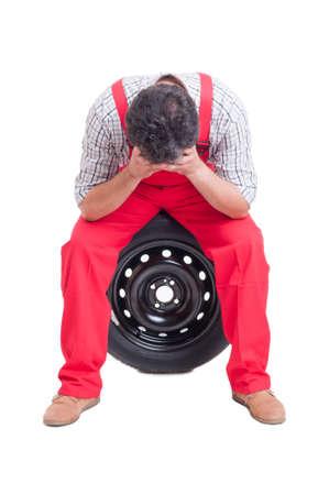 mecanico: Hizo hincapi� en la pista de reclinaci�n mec�nico en las manos y sentado en un neum�tico Foto de archivo