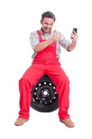 video call: Smiling mechanic making a video call showing like isolated on white Stock Photo