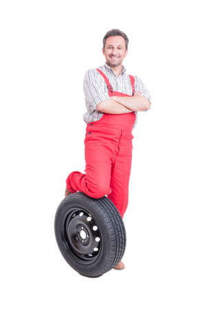 arms crossed: Confident mechanic resting foot on car wheel and arms crossed Stock Photo
