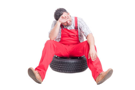sweaty: Tired and exhausted mechanic sitting on a car wheel wiping his sweaty forehead Stock Photo