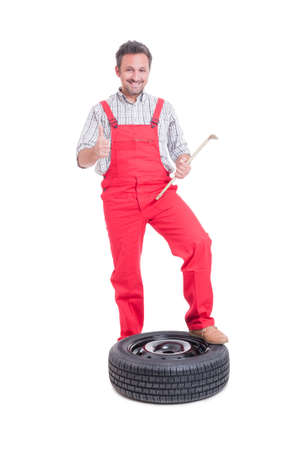 posing  agree: Mechanic changing tire and showing like isolated on white background