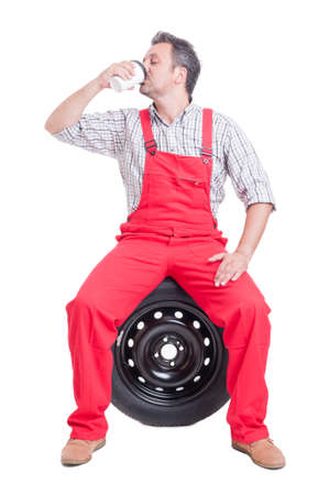 qualified worker: Mechanic drinking coffee to go in a break sitting on car wheel