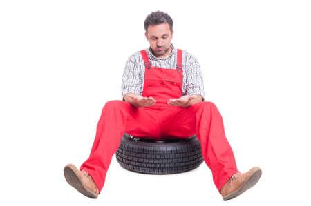 manos sucias: Mecánico Cansado mirándose las manos sucias que se sientan en una rueda de coche Foto de archivo