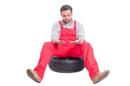 dirty hands: Tired mechanic looking at his dirty hands sitting on a car wheel Stock Photo