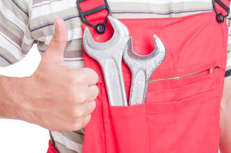 man thumbs up: Like gesture by mechanic or plumber with wrenches inside chest pocket