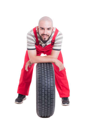 vulcanization: Happy mechanic resting on a new car wheel isolated on white studio background Stock Photo