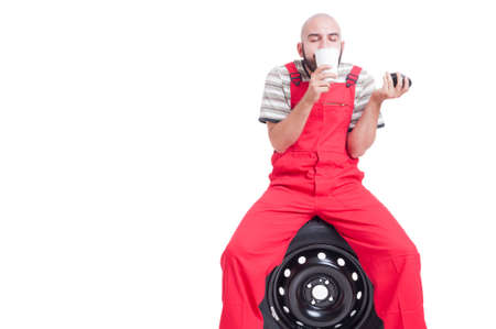taking a break: Young mechanic smelling fresh coffee from a cup while taking a break sitting on car wheel