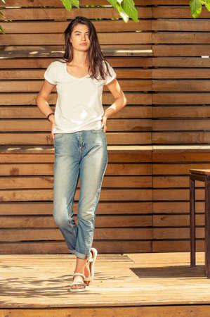 Female model posing outdoor in a sunny day wearing jeans and t-shirt on wooden fence background