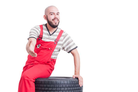 leans on hand: Friendly mechanic offering handshake as deal gesture sitting on car wheel isolated on white Stock Photo